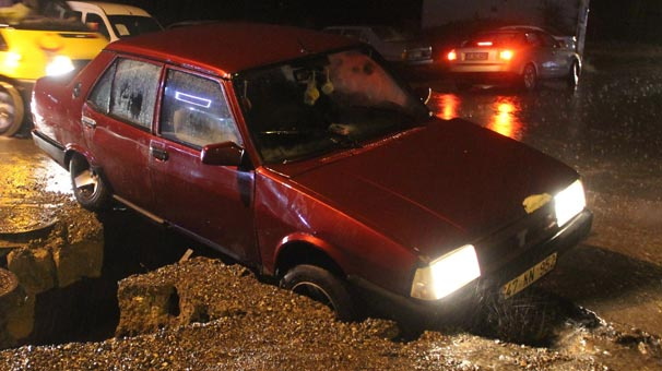 Otomobil yağmur sularının oluşturduğu çukura düştü